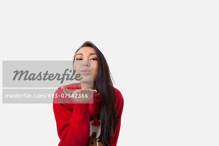 Portrait of woman in Christmas sweater blowing kiss over gray background Stock Photo - Premium Royalty-Free, Image code: 693-07542366