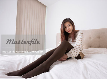 Full length portrait of beautiful young woman in stockings sitting on bed Stock Photo - Premium Royalty-Free, Image code: 693-07672539