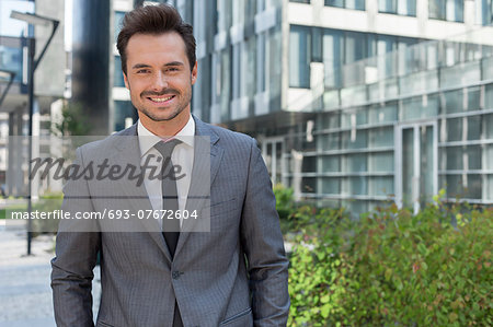 Portrait of smiling young businessman standing against office building Stock Photo - Premium Royalty-Free, Image code: 693-07672604