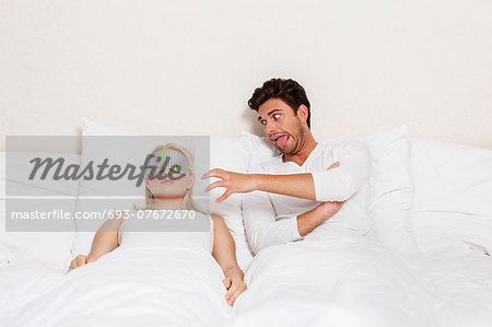 Angry young man teasing sleeping woman in bed Stock Photo - Premium Royalty-Free, Image code: 693-07672670