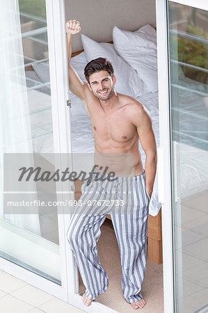 Full length portrait of handsome young man standing at balcony doorway Stock Photo - Premium Royalty-Free, Image code: 693-07672733