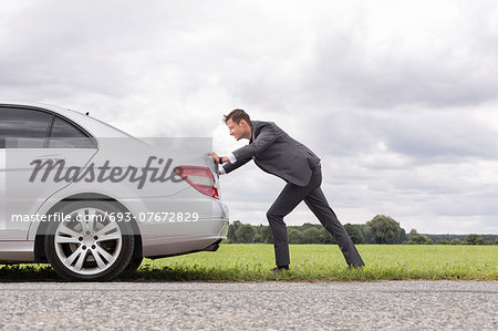 Full length side view of young businessman pushing broken down car on road Stock Photo - Premium Royalty-Free, Image code: 693-07672829