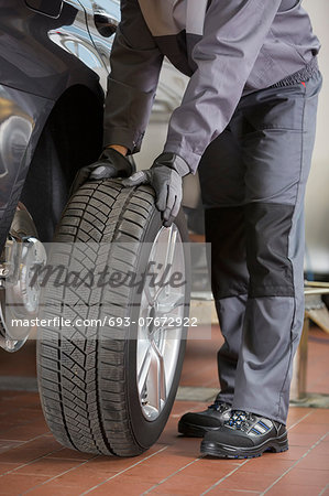 Low section of repairman fixing car's tire in workshop Stock Photo - Premium Royalty-Free, Image code: 693-07672922