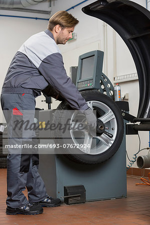 Side view of male mechanic repairing car's wheel in workshop Stock Photo - Premium Royalty-Free, Image code: 693-07672924