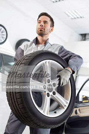 Young maintenance engineer carrying tire in automobile store Stock Photo - Premium Royalty-Free, Image code: 693-07672960