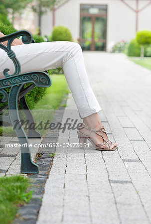 Low section of young woman relaxing on park bench Stock Photo - Premium Royalty-Free, Image code: 693-07673051
