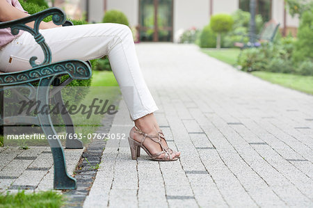 Low section of young woman sitting on park bench Stock Photo - Premium Royalty-Free, Image code: 693-07673052