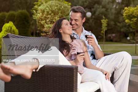 Romantic young holding wine glasses on easy chair in park Stock Photo - Premium Royalty-Free, Image code: 693-07673071