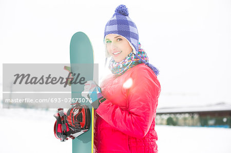Portrait of beautiful young woman holding snowboard in snow Stock Photo - Premium Royalty-Free, Image code: 693-07673076