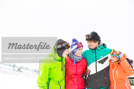 Cheerful young friends standing arm around in snow Stock Photo - Premium Royalty-Free, Image code: 693-07673079