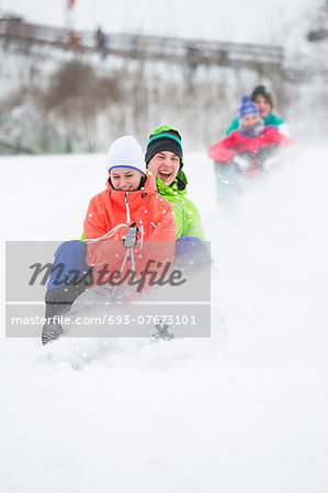 Young couple enjoying sled ride on snow covered slope Stock Photo - Premium Royalty-Free, Image code: 693-07673101