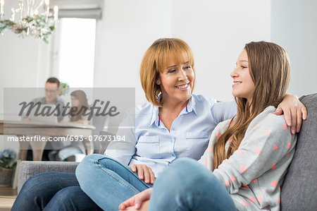affectionate mother and daughter sitting on sofa with family in background Stock Photo - Premium Royalty-Free, Image code: 693-07673194