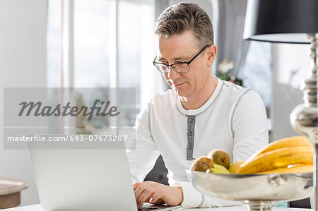 Mature man using laptop at table in house Stock Photo - Premium Royalty-Free, Image code: 693-07673207