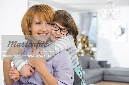 Loving daughter embracing mother at home Stock Photo - Premium Royalty-Free, Image code: 693-07673218