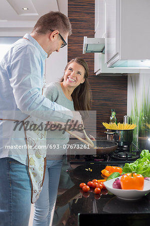 Happy couple preparing food in kitchen Stock Photo - Premium Royalty-Free, Image code: 693-07673261