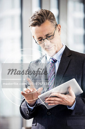 Middle aged businessman using digital tablet in office Stock Photo - Premium Royalty-Free, Image code: 693-07673302
