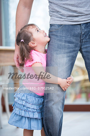 Side view of girl hugging father's leg in house Stock Photo - Premium Royalty-Free, Image code: 693-07912142