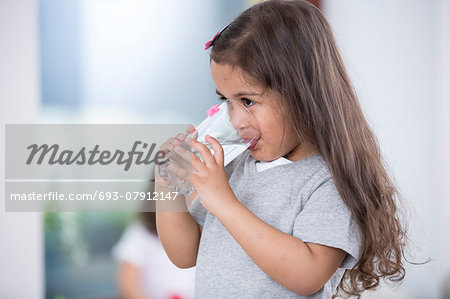 Cute girl drinking glass of water at home Stock Photo - Premium Royalty-Free, Image code: 693-07912147