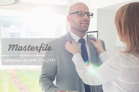 Woman dressing up businessman at home Stock Photo - Premium Royalty-Free, Image code: 693-07912357
