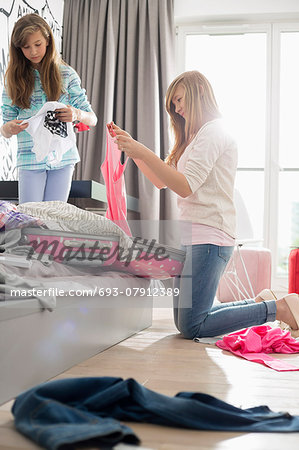 Sisters cleaning bedroom Stock Photo - Premium Royalty-Free, Image code: 693-07912389