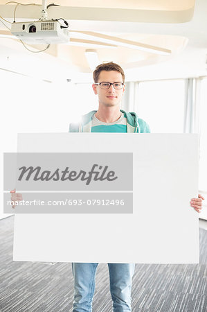 Portrait of confident businessman holding blank board in creative office Stock Photo - Premium Royalty-Free, Image code: 693-07912496