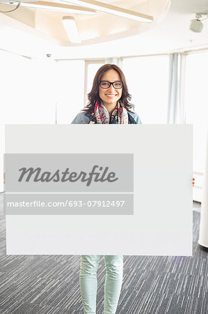 Portrait of happy businesswoman holding blank sign in creative office Stock Photo - Premium Royalty-Free, Image code: 693-07912497
