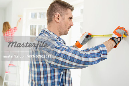 Man measuring wall with woman painting in background