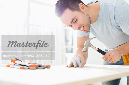 Mid-adult man nailing in table Stock Photo - Premium Royalty-Free, Image code: 693-07912594