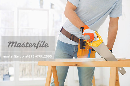 Midsection of man sawing wood in new house Stock Photo - Premium Royalty-Free, Image code: 693-07912595