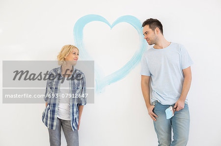 Mid-adult couple looking at each other with painted heart on wall Stock Photo - Premium Royalty-Free, Image code: 693-07912647