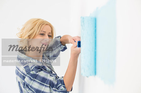 Beautiful woman painting wall with paint roller Stock Photo - Premium Royalty-Free, Image code: 693-07912655