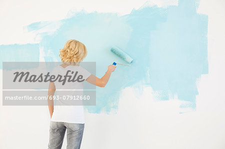 Rear view of woman painting wall with paint roller Stock Photo - Premium Royalty-Free, Image code: 693-07912660