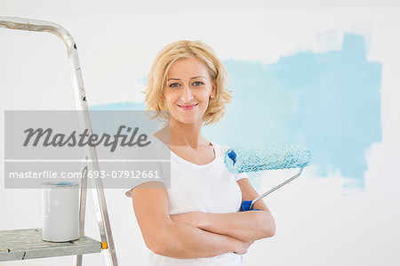 Portrait of woman with paint roller in new house Stock Photo - Premium Royalty-Free, Image code: 693-07912661