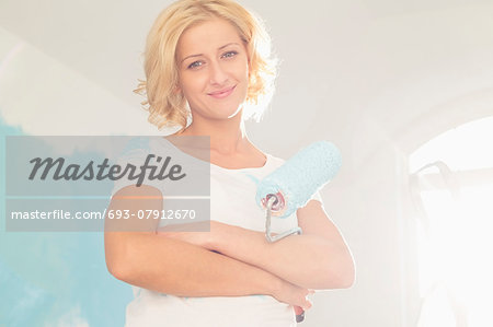 Portrait of woman with paint roller in new house Stock Photo - Premium Royalty-Free, Image code: 693-07912670