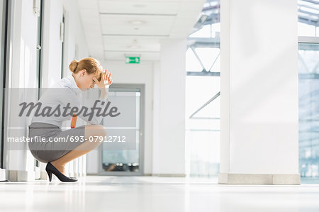 Full-length side view of stressed businesswoman crouching at office hallway Stock Photo - Premium Royalty-Free, Image code: 693-07912712