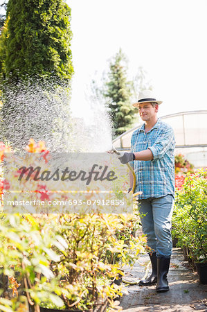 Full-length of man watering plants outside greenhouse Stock Photo - Premium Royalty-Free, Image code: 693-07912855