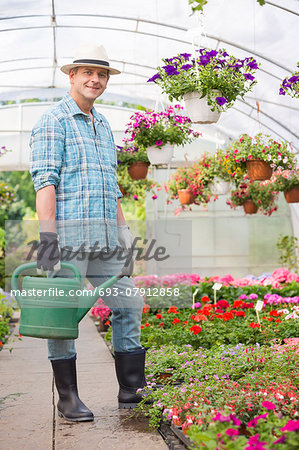 Full-length portrait of smiling man carrying watering can in greenhouse Stock Photo - Premium Royalty-Free, Image code: 693-07912858
