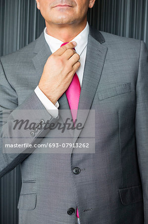 Midsection of mature businessman adjusting necktie Stock Photo - Premium Royalty-Free, Image code: 693-07913262