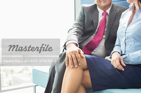 Midsection of businessman flirting with female colleague in office Stock Photo - Premium Royalty-Free, Image code: 693-07913295