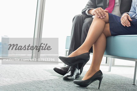 Low section of businessman flirting with female colleague in office Stock Photo - Premium Royalty-Free, Image code: 693-07913296