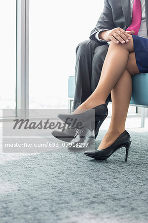 Low section of businessman flirting with female colleague in office Stock Photo - Premium Royalty-Free, Image code: 693-07913297
