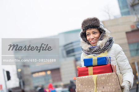 Happy woman looking away while carrying stacked gifts during winter Stock Photo - Premium Royalty-Free, Image code: 693-08126888