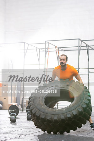 Dedicated man flipping tire in crossfit gym Stock Photo - Premium Royalty-Free, Image code: 693-08126938