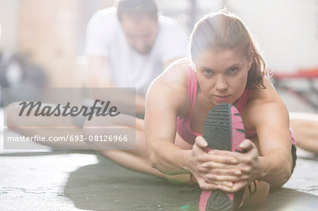 Portrait of confident woman doing stretching exercise in crossfit gym Stock Photo - Premium Royalty-Free, Image code: 693-08126966