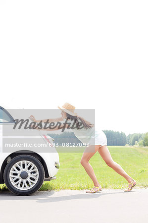 Side view of woman pushing broken down car on country road Stock Photo - Premium Royalty-Free, Image code: 693-08127093