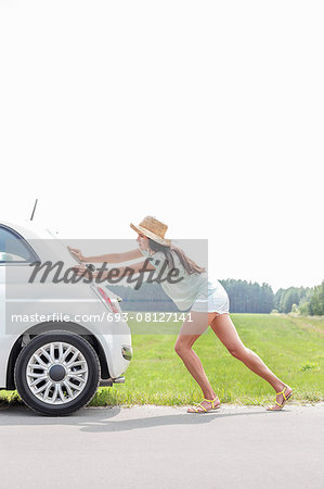 Full-length of woman pushing broken down car on country road Stock Photo - Premium Royalty-Free, Image code: 693-08127141
