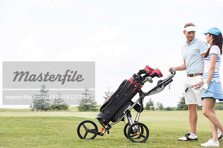 Friends with equipment talking while walking at golf course against clear sky Stock Photo - Premium Royalty-Free, Image code: 693-08127234