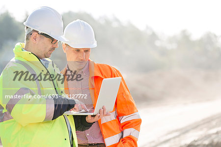 Supervisors using laptop at construction site Stock Photo - Premium Royalty-Free, Image code: 693-08127772