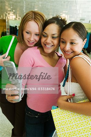 3 Girl friends Posing for Camera Phone Picture in clothing store Stock Photo - Premium Royalty-Free, Image code: 694-03318474