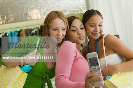 3 Girl friends Posing for Camera Phone Picture in clothing store Stock Photo - Premium Royalty-Free, Image code: 694-03318486